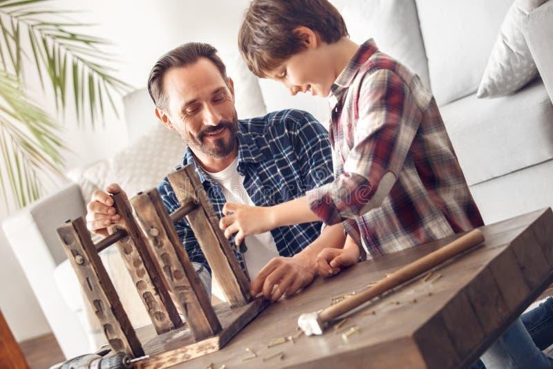 在家站立与螺丝刀愉快的配合的父亲和一点儿子拧紧的钉子 免版税库存照片
