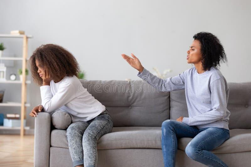在家责骂青少年的女儿的恼怒的积极的母亲 库存照片