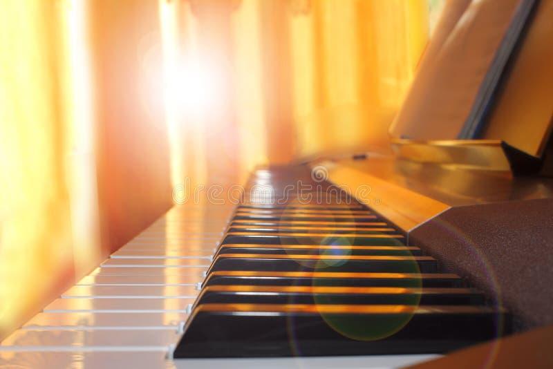在家钢琴培训班前的钢琴钥匙,关闭在太阳的光芒,被定调子 免版税库存图片