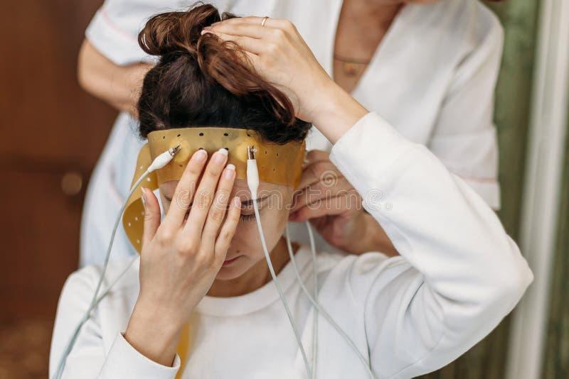 在实验室年轻女人佩带的脑波扫描耳机在与闭合的眼睛的一把椅子坐 在脑子神经学研究 免版税库存图片