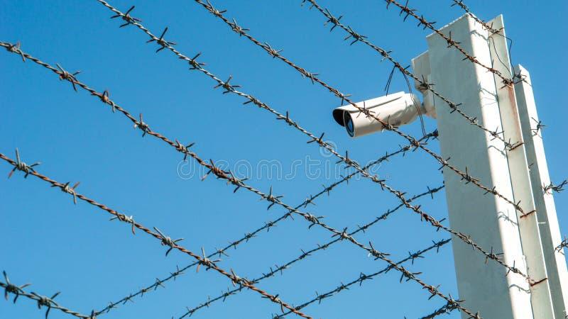 在安检区域和拷贝空间铁丝网篱芭的CCTV监视安全监控相机视频器材  免版税库存照片