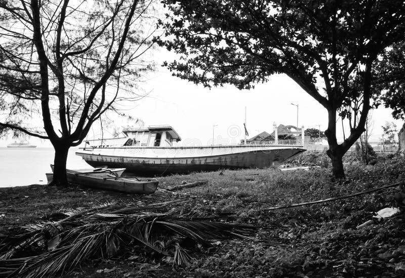 在安静的黄色沙滩的黑白生锈和被放弃的船在新鲜的早晨日出空气 库存照片