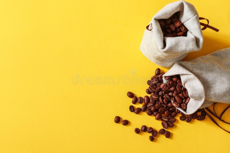 在小大袋的烤咖啡豆在黄色背景 免版税库存图片