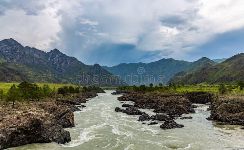 在山的剧烈的雷暴云彩在卡通河的上部伸手可及的距离在阿尔泰 库存图片