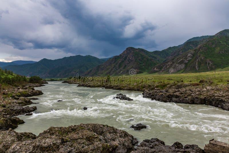 在山的剧烈的雷暴云彩在卡通河的上部伸手可及的距离在阿尔泰 免版税库存图片