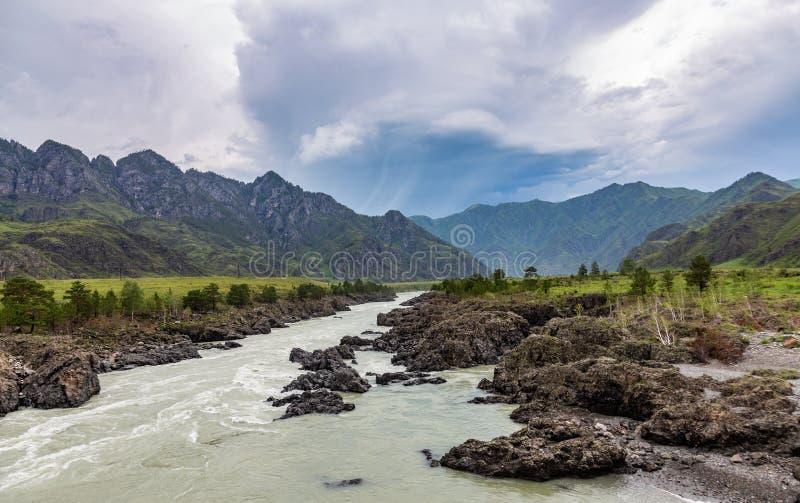 在山的剧烈的雷暴云彩在卡通河的上部伸手可及的距离在阿尔泰 图库摄影