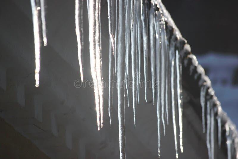 在屋顶的水下落 冰柱熔化在暖气和太阳的影响下 春天影响在世界上 修改毛孔  免版税库存照片