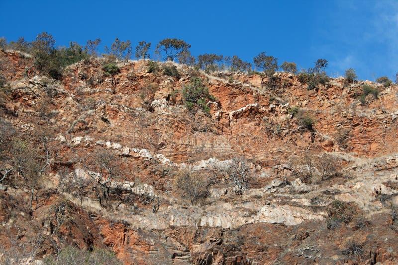 在岩石面孔反对小山-白色石英岩&红色页岩的被区分的层数 库存图片