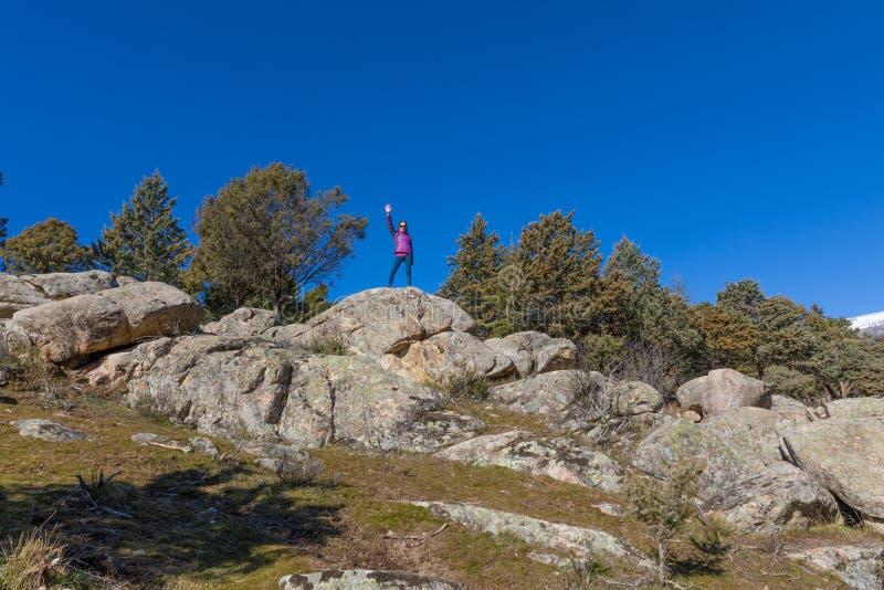 在岩石顶部的妇女向致敬用手的在山 免版税库存图片