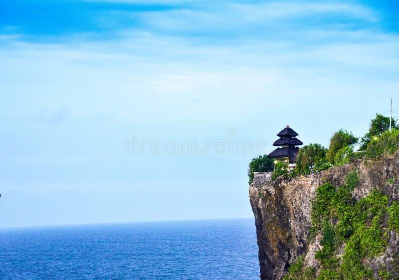 在峭壁的Goregeous浪漫日落在与神圣的寺庙的山顶部在上面 免版税库存图片