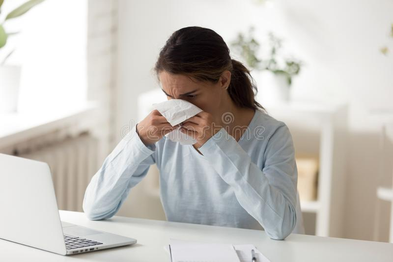 在工作场所吹的鼻子的不健康的女性开会 免版税库存照片
