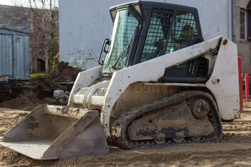 在工地工作的小excavatot 免版税图库摄影