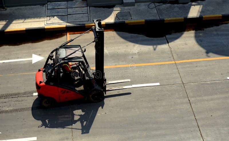 在工厂路的红色铲车 免版税库存图片