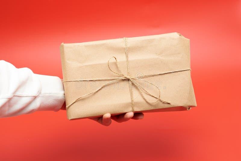在工艺纸包裹的礼物在一个人的手上红色背景的 免版税图库摄影
