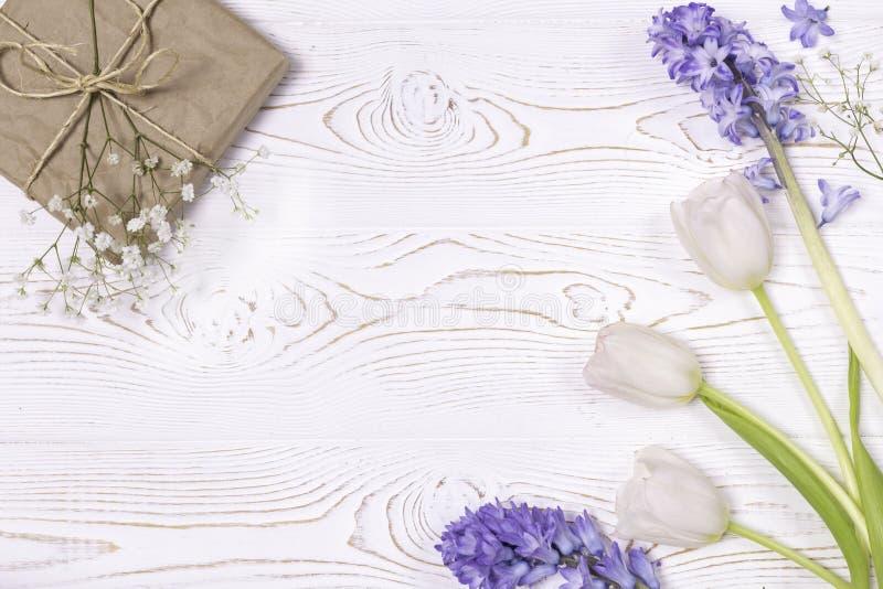 在工艺纸和蓝色风信花花包裹的礼物盒,在白色台式的白玫瑰 平的位置 复制空间为 库存照片