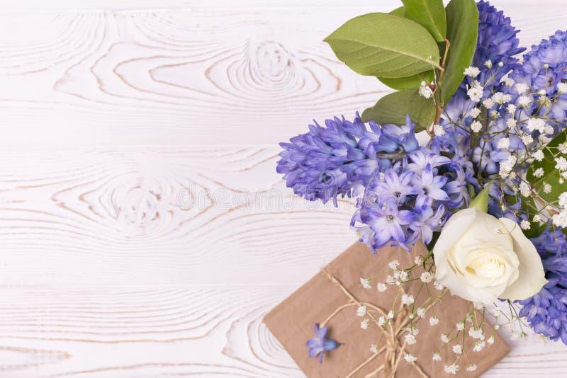 在工艺纸和蓝色风信花花包裹的礼物盒,在白色台式的白玫瑰 平的位置 复制空间为 免版税库存照片