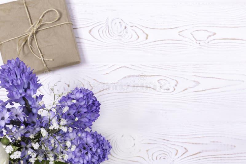 在工艺纸和蓝色风信花花包裹的礼物盒,在白色台式的白玫瑰 平的位置 复制空间为 免版税图库摄影