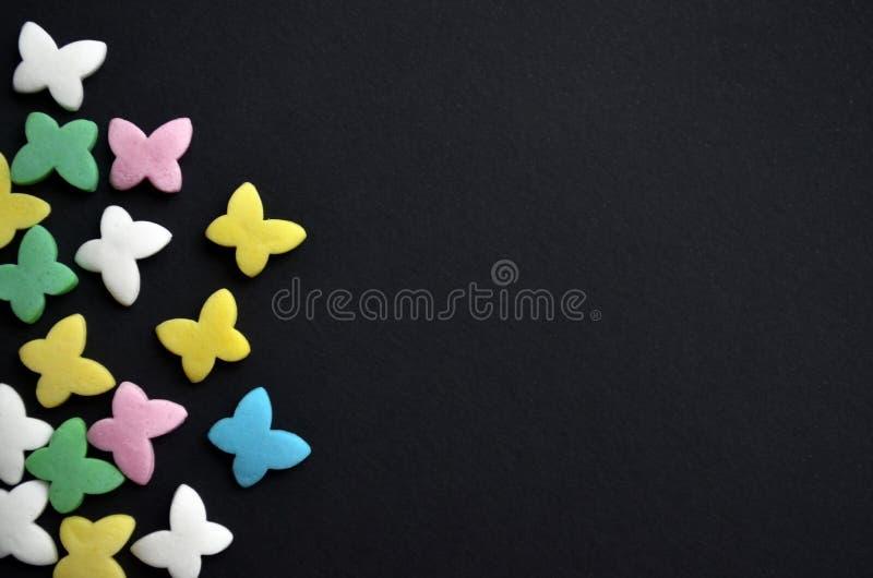 在左边的糖多彩多姿的蝴蝶在黑背景、春天的与copyspace的概念和3月8日, 免版税库存图片