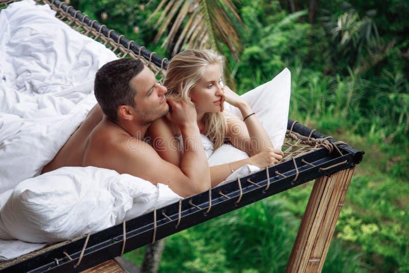 在巴厘岛,Ubud的蜜月 成功的夫妇放松在别墅的,美丽的景色 免版税库存照片