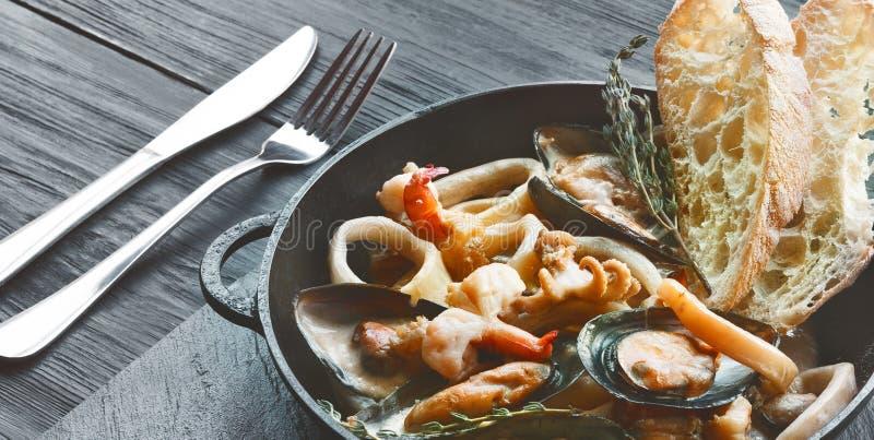 在平底深锅特写镜头的海鲜炖煮的食物在黑暗的木背景 库存图片
