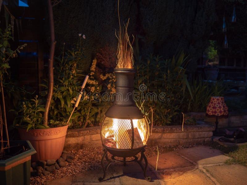 在庭院chiminea附近的晚上 库存照片