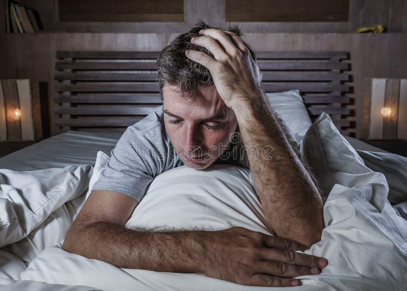 在床感觉担心的遭受的消沉问题和忧虑的年轻可爱的哀伤和沮丧的人剧烈的画象  库存照片