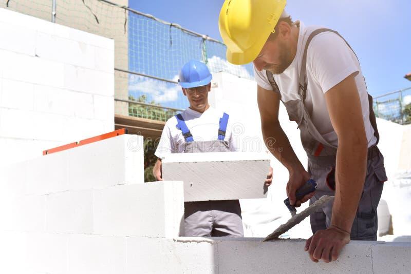 在建筑工地的配合-建筑工人修建房子 免版税库存图片