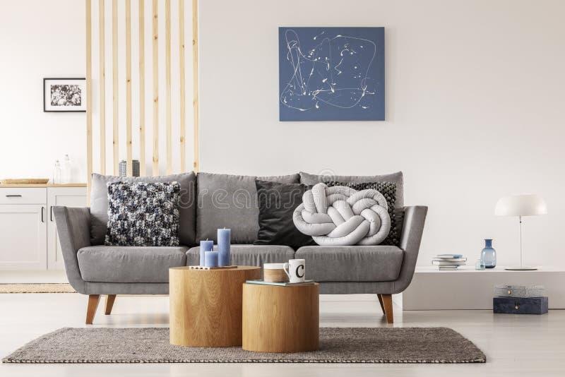 在当代客厅白色墙壁上的蓝色抽象绘画内部与与枕头的灰色长椅 库存照片