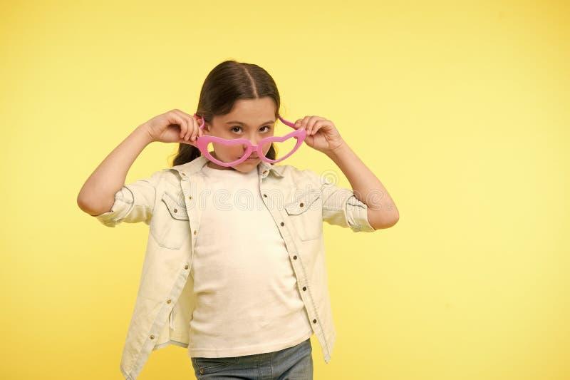 在心形的玻璃的女孩神色在黄色背景 有时装配件的小孩 保留安静并且佩带凉快 免版税库存图片