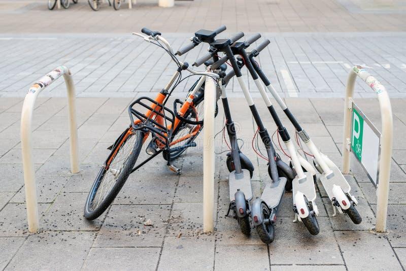 在城市街道上和电滑行车停放的自行车 自助街道运输出租服务 租都市车 免版税库存照片