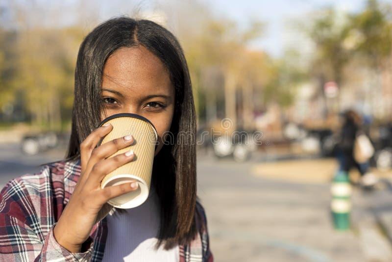 在城市街道的年轻非裔美国人的妇女身分,当对负拿走咖啡和看照相机在一好日子时 库存照片