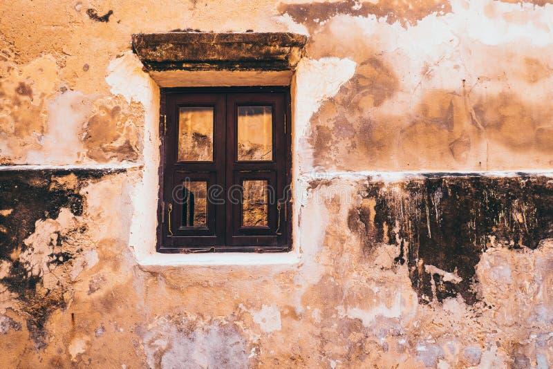 在土气黄色混凝土墙门面背景的葡萄酒口气老白色木窗口 库存照片