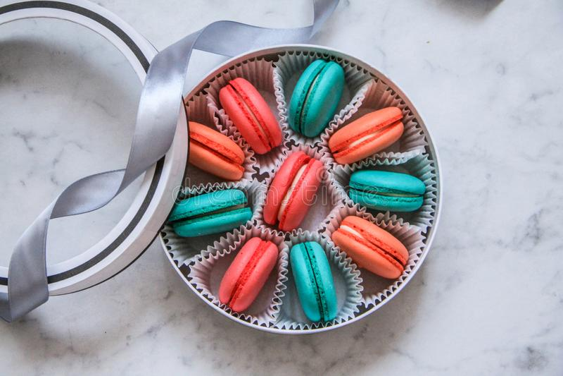 在圆的白色箱子的多彩多姿的可口自创macarons在大理石背景 免版税库存照片