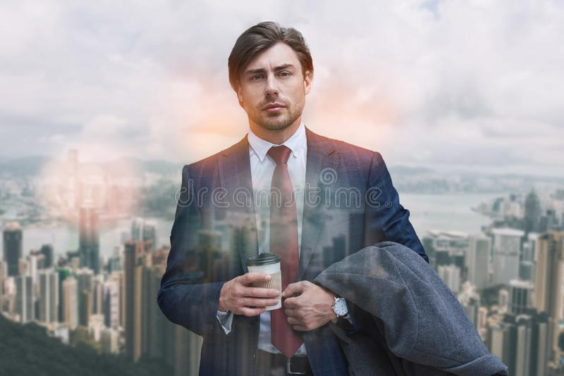在去的咖啡休息 确信的商人藏品咖啡画象,当站立户外与现代办公室时 免版税库存图片