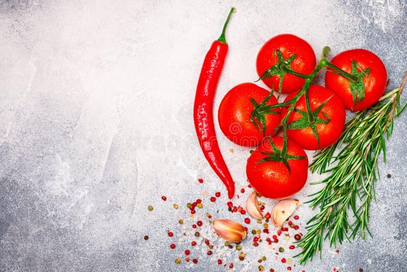 在分支、红辣椒、迷迭香、大蒜和香料的新鲜的水多的成熟蕃茄 免版税库存照片
