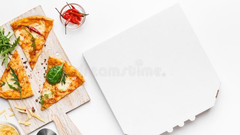 在切板和空的纸板箱的比萨切片 免版税库存图片