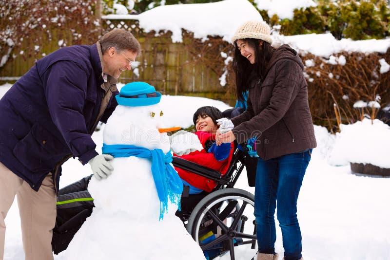 在冬天期间,轮椅大厦雪人的残疾男孩与家庭 库存图片
