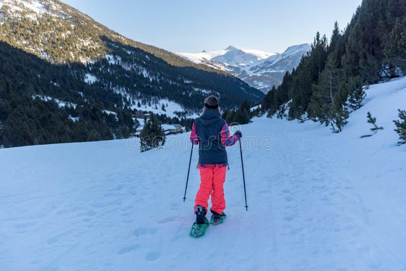 在冬天足迹的年轻女人实践的雪靴 免版税库存照片