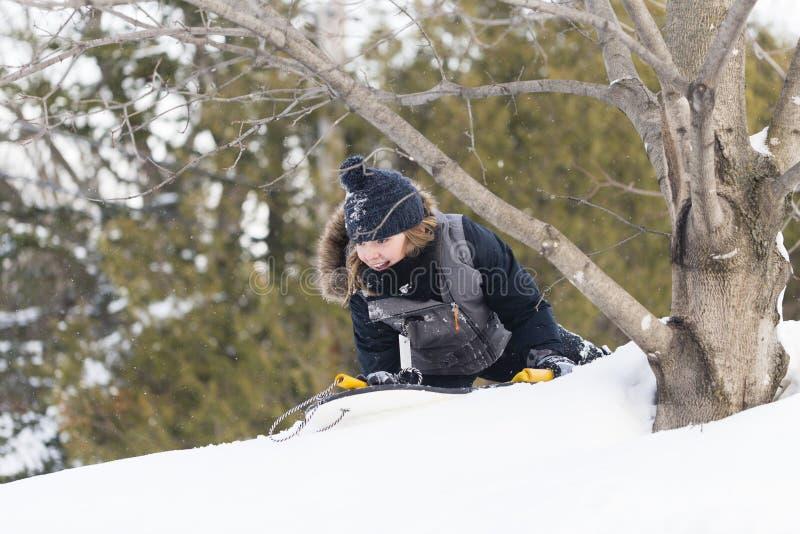 在冬季衣服打扮的女孩微笑,当准备滑下来一个多雪的倾斜时 免版税库存照片