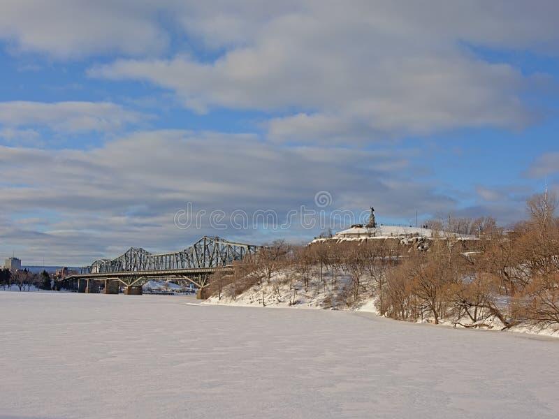 在冻结的渥太华河和Nepean监视点的亚历山德拉省际的桥梁在与雪的冬日 图库摄影