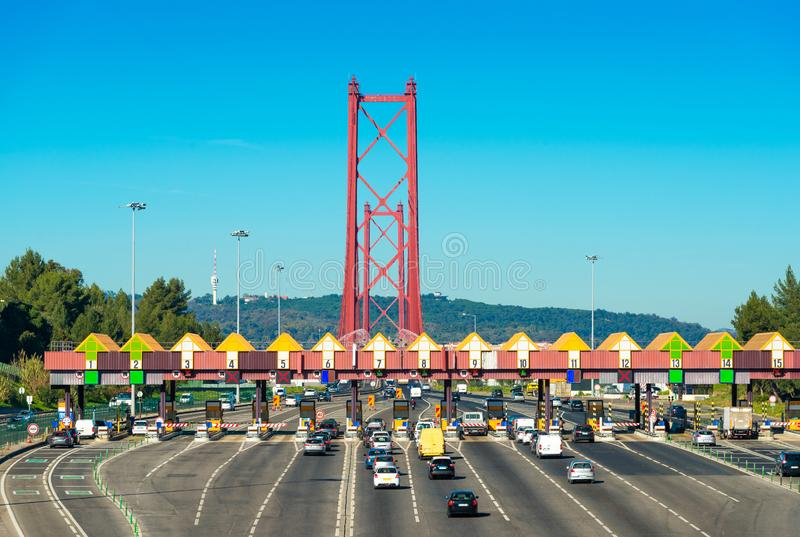 在入口的通行费驻地对在里斯本和阿尔马达,葡萄牙之间的4月25日桥梁 穿过薪水驻地的汽车 图库摄影