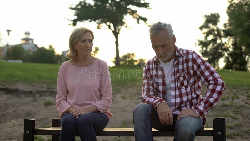 在关系、退休的男人和妇女的危机坐长凳在公园,争吵 库存图片