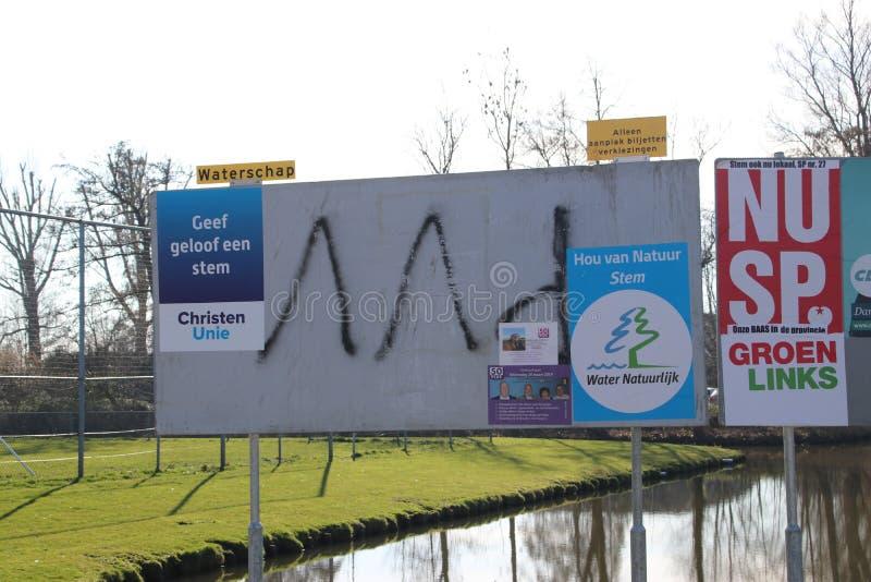 在党黏贴的公开广告牌的竞选活动海报在nIeuwerkerk aan小室Ijssel在荷兰 免版税图库摄影