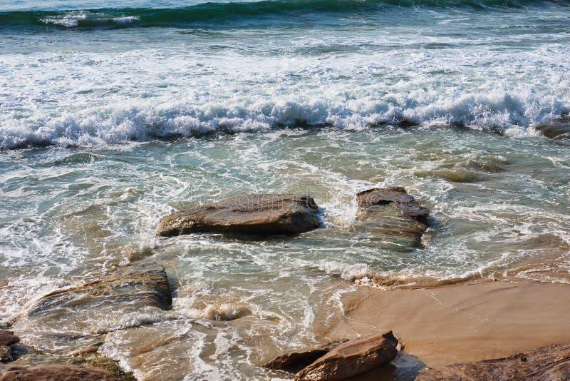 在克罗纳拉海滩岩石和沙子,悉尼,澳大利亚的太平洋波浪 免版税图库摄影