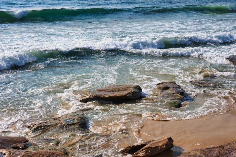 在克罗纳拉海滩岩石和沙子,悉尼,澳大利亚的太平洋波浪 免版税库存照片