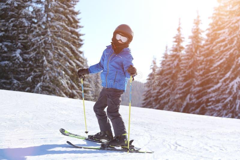 在倾斜的小男孩滑雪在山滑雪场 免版税库存照片