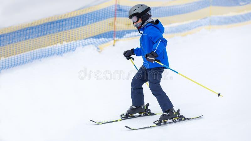 在倾斜的小男孩滑雪在山滑雪场 免版税库存图片