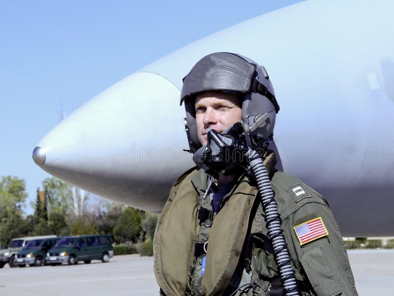 在喷气式歼击机前面的美国军事飞行员 免版税库存照片