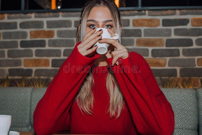 在咖啡馆的少妇饮用的咖啡 免版税库存图片