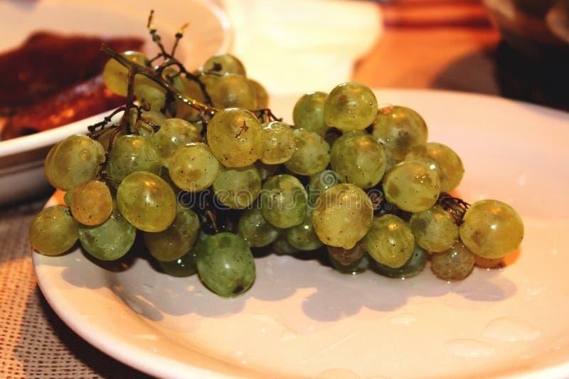 在板材的美味和水多的葡萄在家 库存照片